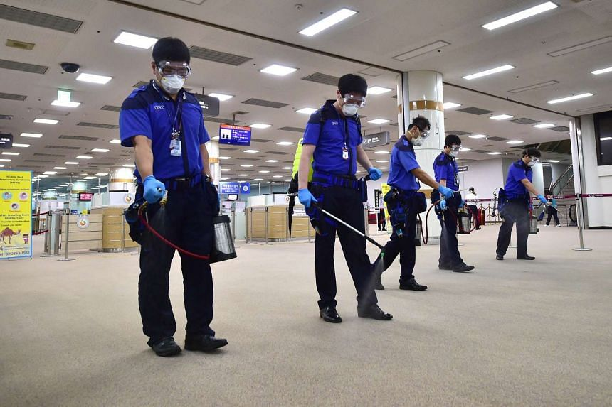 In a file photo taken on June 17, 2015, South Korean workers spray antiseptic solution at the customs, immigration and quarantine office of Gimpo international airport in Seoul.