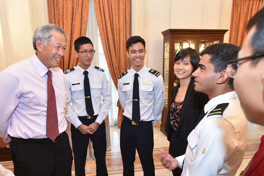 Defence Minister Ng Eng Hen (left) speaking with Singapore Armed Forces (SAF) and Ministry of Defence (Mindef) scholarship holders at the award ceremony at the Istana on Wednesday, July 29, 2015