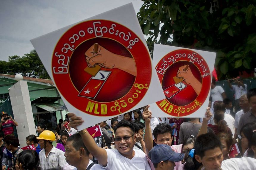 National League for Democracy supporters hold up posters in support of party chairman Aung San Suu Kyi (not pictured) after she submitted her application to run as a candidate in the 2015 general election, in Yangon on July 29, 2015.