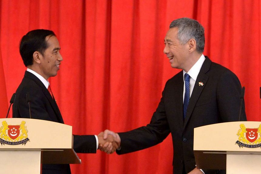 Prime Minister Lee Hsien Loong shaking hands with Indonesian President Joko Widodo after a joint news conference at the Istana yesterday.
