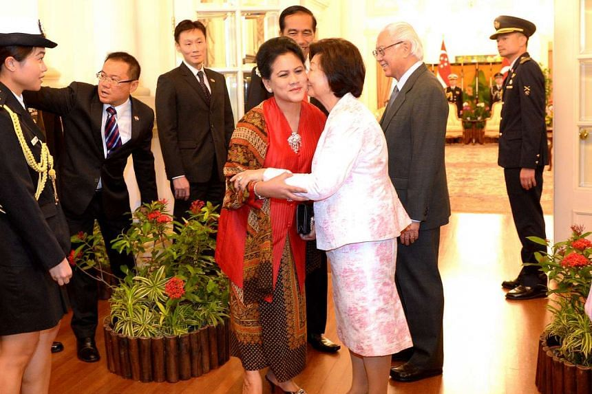President Tony Tan Keng Yam and Indonesian President Joko Widodo are all smiles as their respective spouses Mary Tan and Iriana Joko Widodo share a warm embrace at the Istana yesterday. The Indonesian First Couple are on an official visit to Singapor