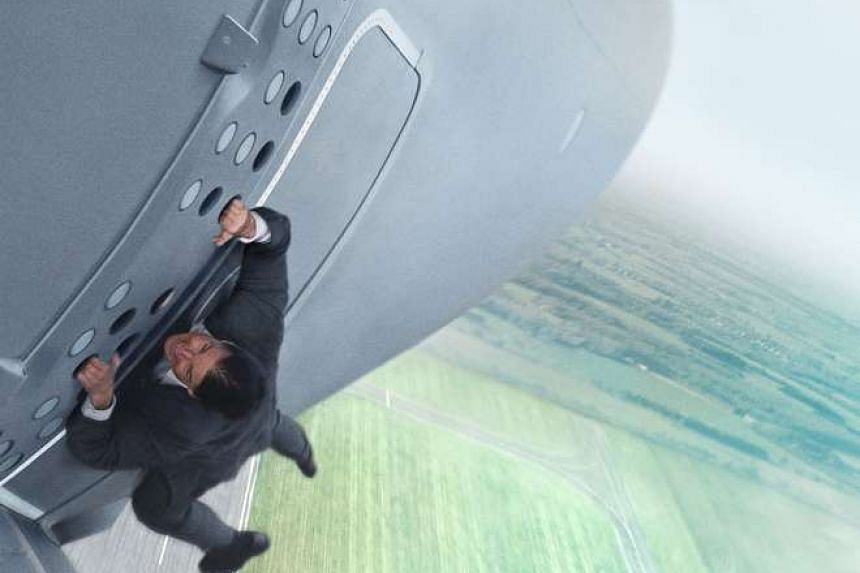 Tom Cruise hanging onto an airborne plane in Mission: Impossible – Rogue Nation.
