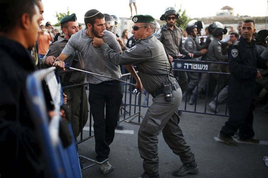 A Jewish settler (second left) scuffles with an Israeli border police officer near buildings slated for demolition by order of Israel's high court, in the West Bank Jewish settlement of Beit El, near Ramallah on July 28, 2015.