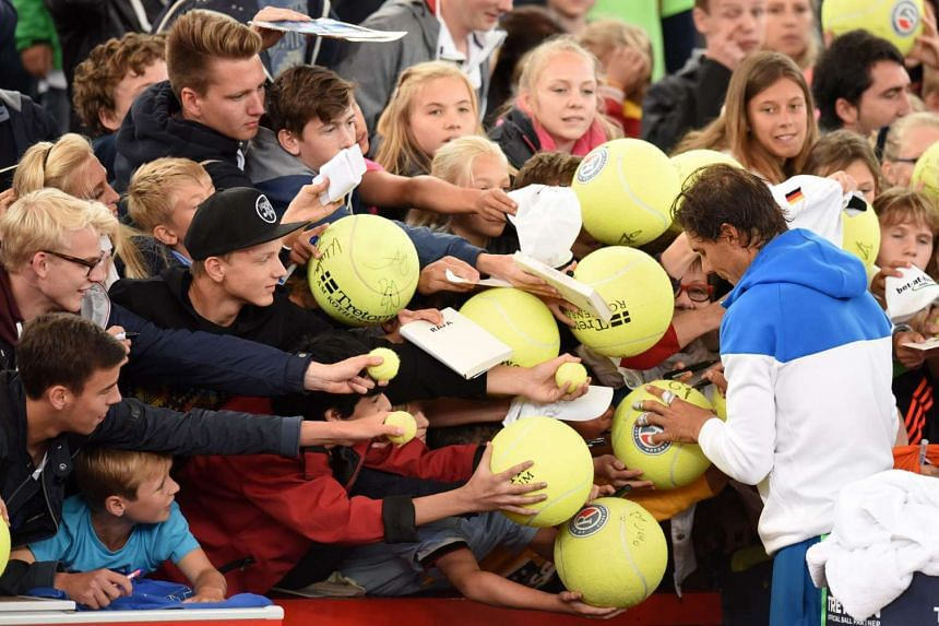 Rafael Nadal of Spain signs autographs after winning against compatriot Fernando Verdasco in their first round match at the ATP tennis tournament in Hamburg, Germany, on July 28, 2015.