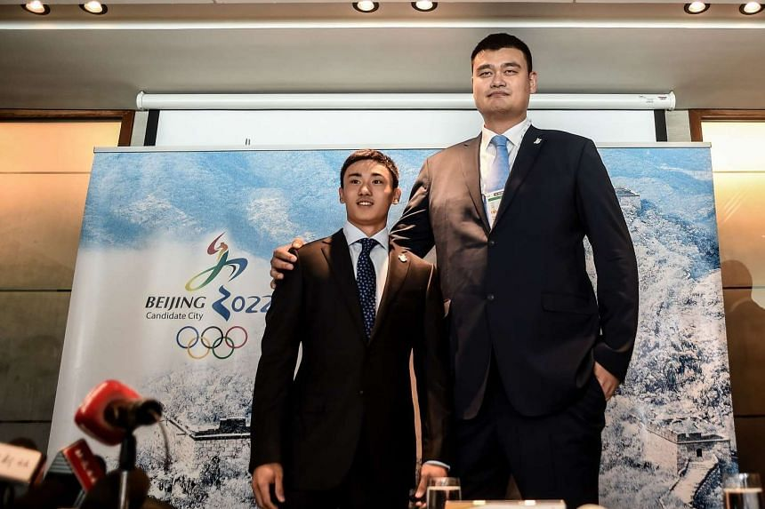 Retired Chinese professional basketball player Yao Ming (right) and ice hockey player Song Andong (left) pose prior to a Beijing 2022 Olympics bid committee press briefing in Kuala Lumpur on July 29, 2015.