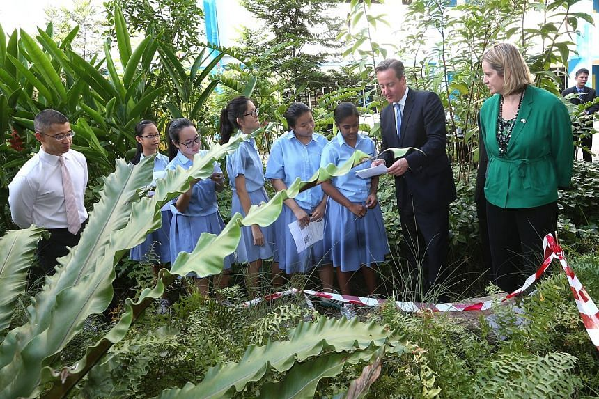 Left: British PM David Cameron and Secretary of State for Energy and Climate Change Amber Rudd joining students from Commonwealth Secondary at an outdoor biology lesson yesterday, with principal Aaron Loh (far left). Below: Mr Cameron and PM Lee Hsie