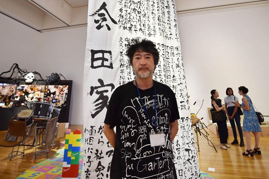 Artist Makoto Aida with his calligraphy work that mildly mocks Japan's education ministry.
