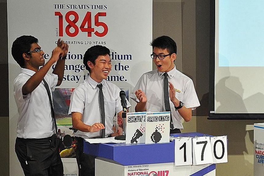 Pioneer JC Team 1's (from left) Elango Praveen, Joshua Goh and Jerald Ang celebrating after getting the correct answer in the final stretch of the ST-MOE National Current Affairs Quiz yesterday.