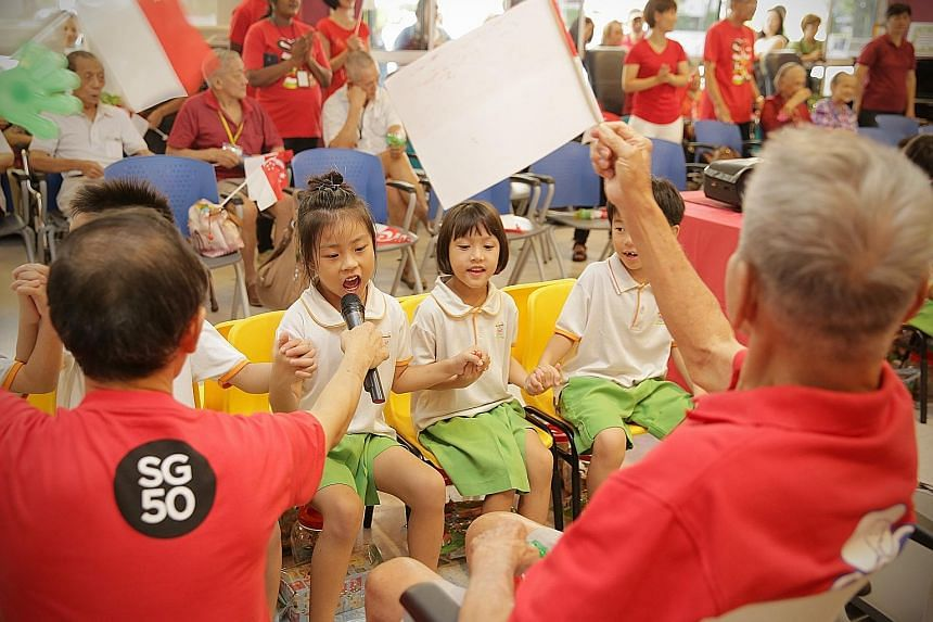 Kindergarten children from My First Skool singing SG50 songs with seniors from NTUC Health's Silver Circle Senior Care Centre, in an inter-generational bonding event yesterday. For about three months, 50 senior citizens from the centre and 50 childre