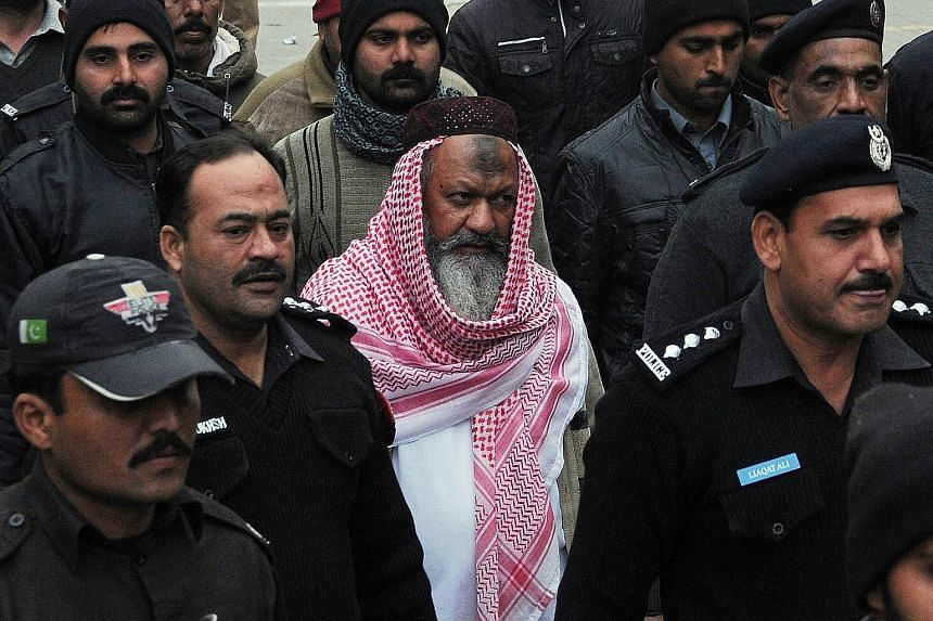 Malik Ishaq, head of the Lashkar-e- Jhangvi, being escorted to court in Lahore last December. Ishaq had faced several murder trials but had always been acquitted after witnesses refused to testify.