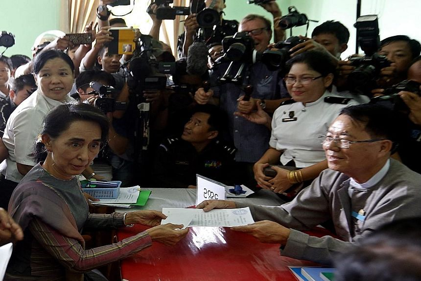 Myanmar opposition leader Aung San Suu Kyi at an Election Commission office in a Yangon township yesterday to submit an application to run in the Nov 8 general election.