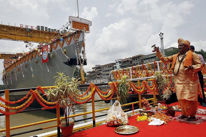 A Hindu priest blessing the Kavaratti, one of the Indian Navy's four anti-submarine warfare corvettes, during its launch at a dockyard in Kolkata. India plans to spend at least US$61 billion (S$83 billion) on expanding its navy's size by about half i