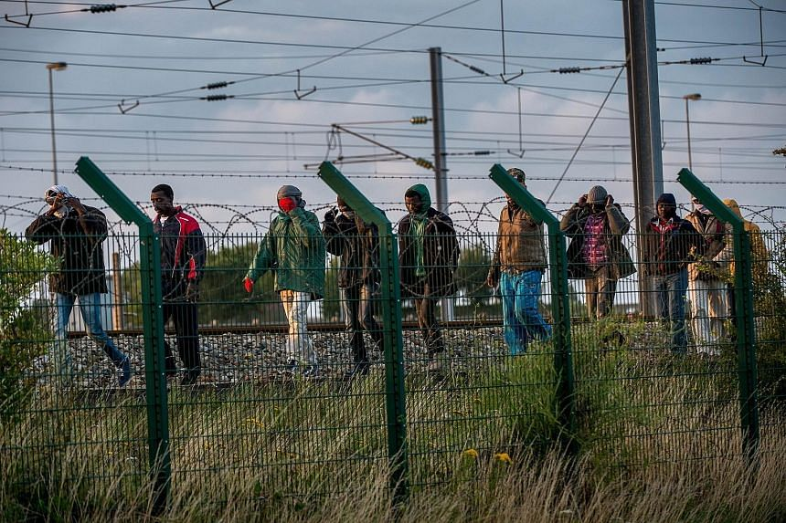 Illegal migrants who successfully got into the Eurotunnel terminal in France on Tuesday walking along a railroad track as they try to reach a shuttle to Britain. An official count early this month showed about 3,000 migrants - mainly from Ethiopia, E