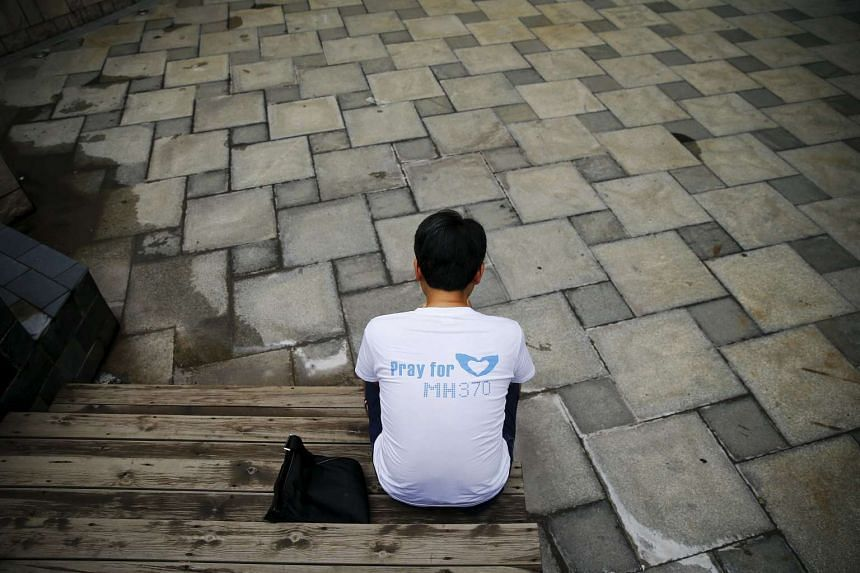 Jiang Hui, whose mother was onboard the missing Malaysia Airlines flight MH370, check the news on his mobile phone before talking to reporters near his home in Beijing on July 30, 2015.