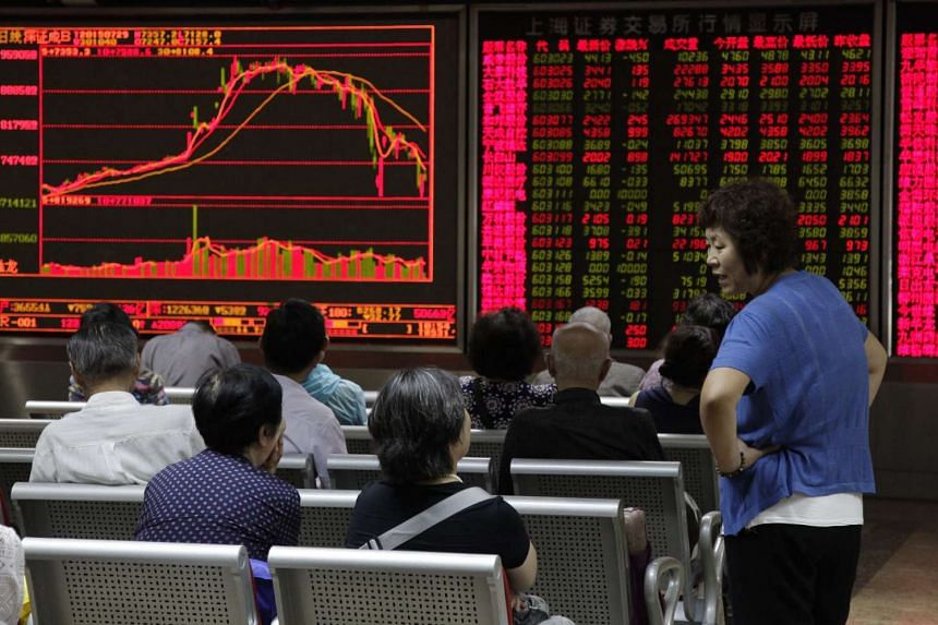 Investors monitor stock market data displayed on an electronic board at a securities brokerage house in Beijing, China on July 29, 2015.