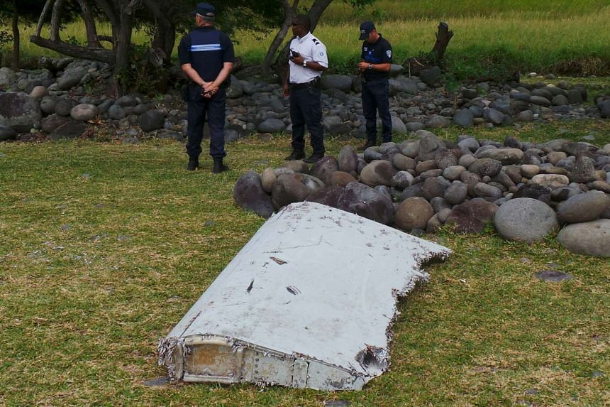 French gendarmes and police stand near a large piece of plane debris which was found on the beach in Saint-Andre, on the French Indian Ocean island of La Reunion on July 29, 2015.