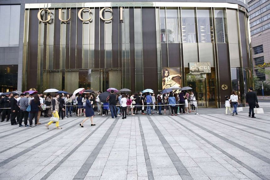 Customers line up as they wait to go into a Gucci store in Shanghai on May 27, 2015.