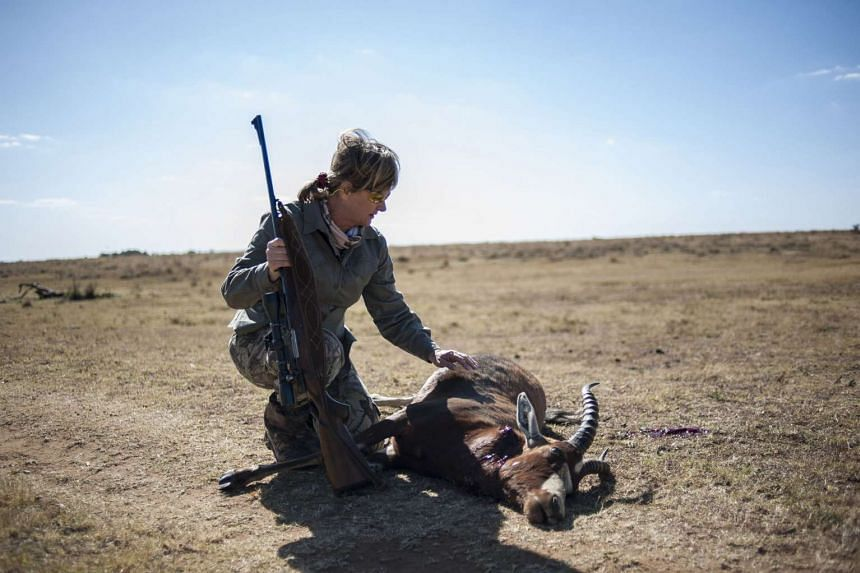 Adri Kitshoff, of the Professional Hunters' Association of South Africa, kneels by an antelope she hunted at the Iwamanzi Game Reserve in Koster.