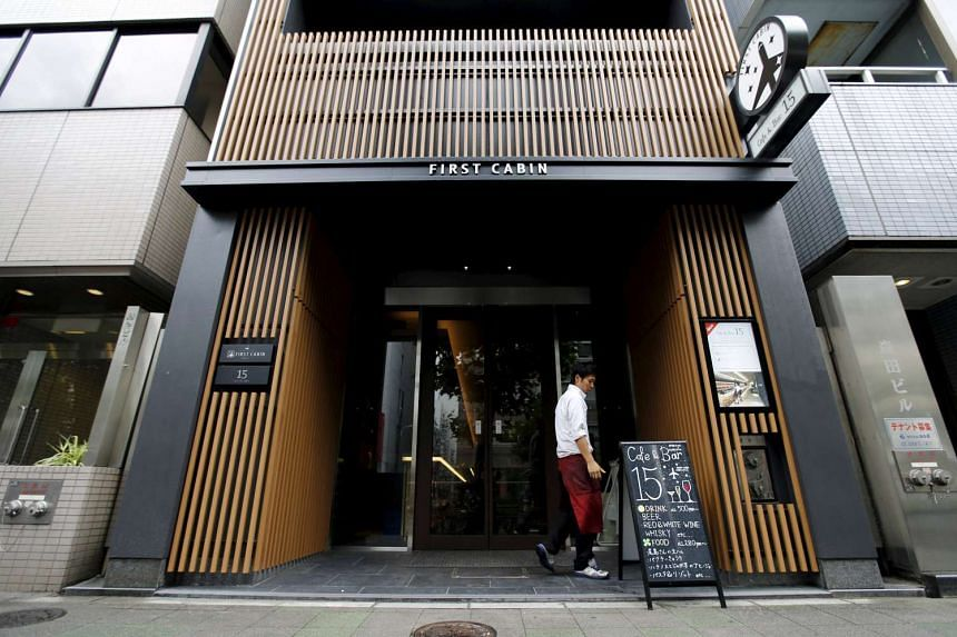 A man walks near the entrance of First Cabin hotel, which was converted from an old office building, in Tokyo.