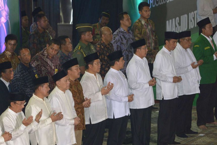 President Joko Widodo (front row, third from right) attends a mass prayer held by members of NU, the biggest Muslim organisation in Indonesia, to welcome Ramadan in Jakarta on June 14, 2015.
