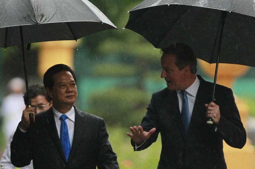 British PM David Cameron (right) chats with Vietnamese counterpart Nguyen Tan Dung while walking in the garden of the Presidential Palace in Hanoi.