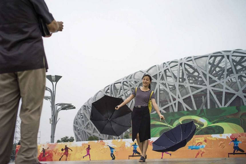 A woman poses in front of the Bird's Nest stadium in Beijing on July 30, 2015.