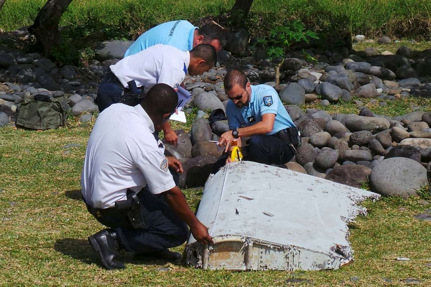 French gendarmes and police inspect a large piece of plane debris which was found on the French Indian Ocean island of La Reunion on July 29, 2015.