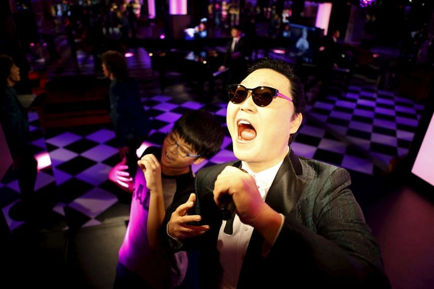 A boy poses for photographs next to the wax figure of South Korean singer Psy at Grevin Wax Museum in central Seoul, South Korea, on July 30, 2015.