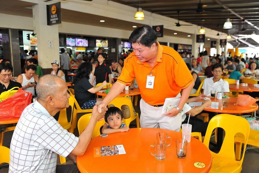 NSP president Sebastian Teo (center, standing) interacts with a resident during a walkabout around Tampines Street 81 on July 26, 2015.