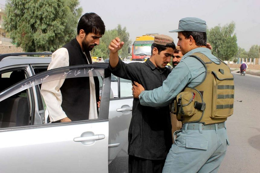 Afghan security official frisk a man on a roadside as security has been intensified after reports on the death of Mullah Omar, the secretive leader of the Afghan Taliban.