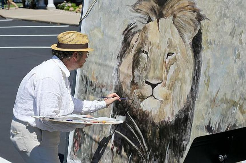 Painter Mark Balma paints a portrait of Cecil the lion to donate to anti-poaching efforts in the parking lot of Dr Walter Palmer's dental clinic.
