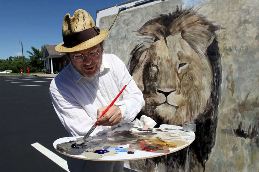 Mark Balma, an international artist based in California and Florence, Italy, paints a lion head on a canvas in the parking lot of River Bluff Dental clinic in protest against the killing of a famous lion in Zimbabwe.