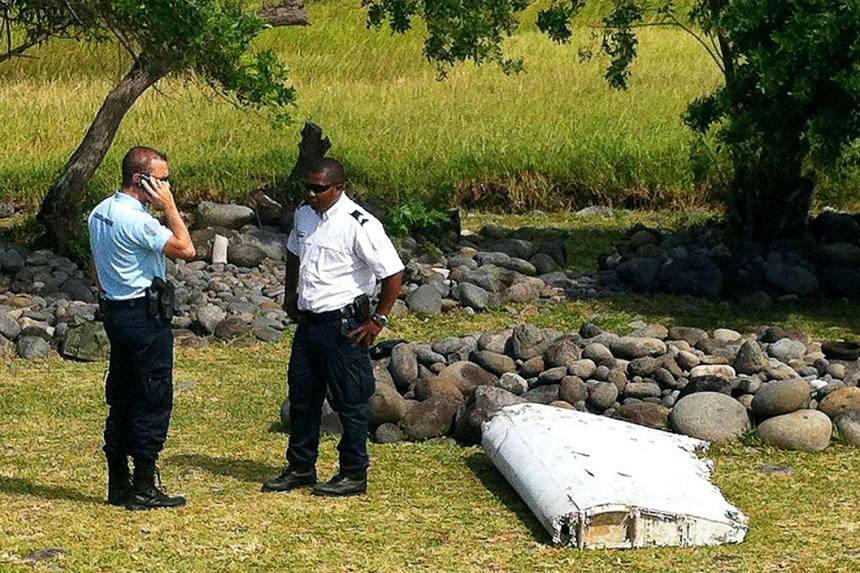 Policemen standing next to a piece of debris from an unidentified aircraft found in the coastal area of Saint-Andre de la Reunion.