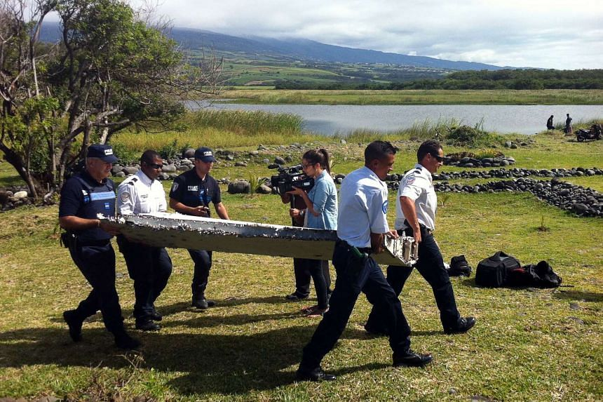 Police carry a piece of debris from an unidentified aircraft found on Reunion Island on July 29, 2015.