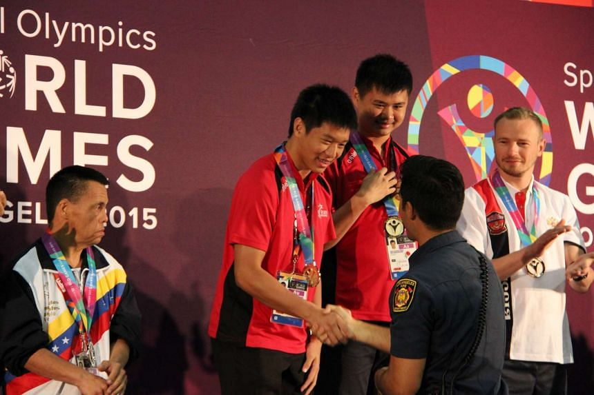 Unified partner Bertrand Yan (left) and Special Olympics athlete Poh Wei Xiang receiving their Gold medals.