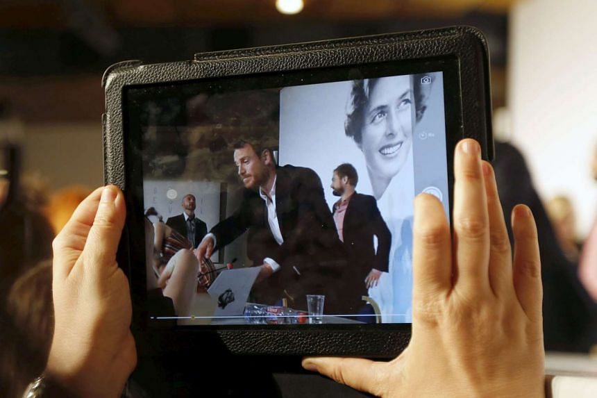 A journalist takes a picture with a tablet device as actor Michael Fassbender signs autographs at the Cannes Film Festival in May 2015.