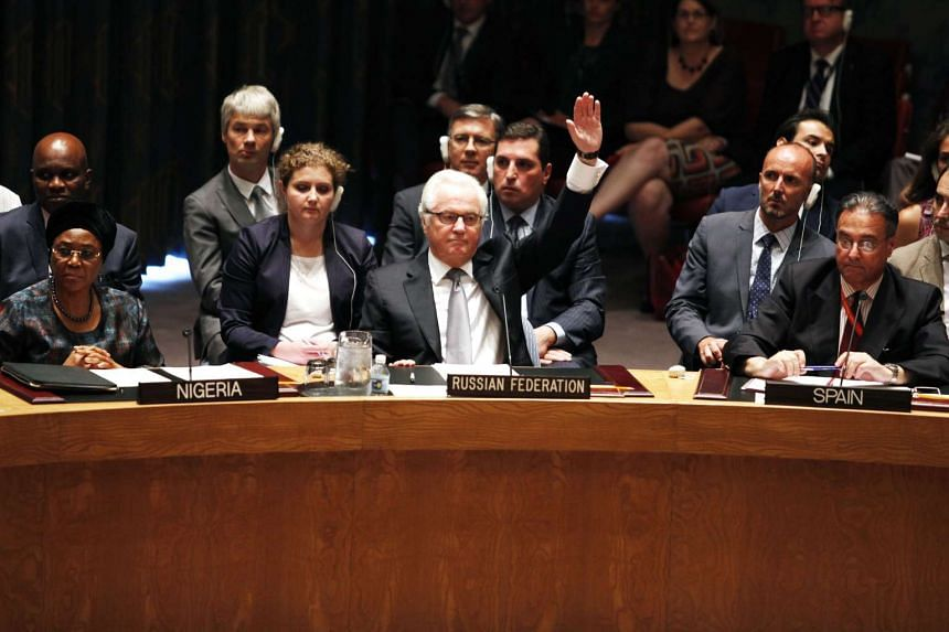 Russian ambassador Vitaly Churkin votes to veto on a draft resolution for establishing a tribunal to prosecute those responsible for the MH17 flight at the United Nations Headquarters in New York on July 29, 2015.