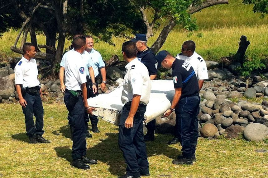 Policemen and gendarmes stand next to a piece of debris from an unidentified aircraft found in the coastal area of Saint-Andre de la Reunion.