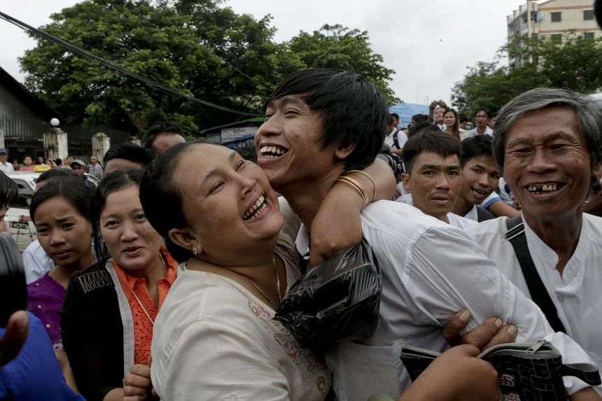 Journalist Min Wa Than (right), is greeted by his sister as he leaves Insein Prison in Yangon, Myanmar on July 30, 2015.