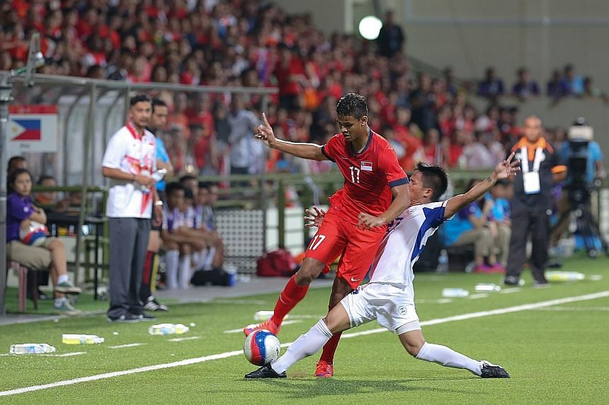 Singapore U-23 forward Irfan Fandi charging down the flanks during the SEA Games football match against the Philippines, as his coach Aide Iskandar (in white) looks on. The Young Lions' failure to make the SEA Games semi-finals was a bitter disappoin