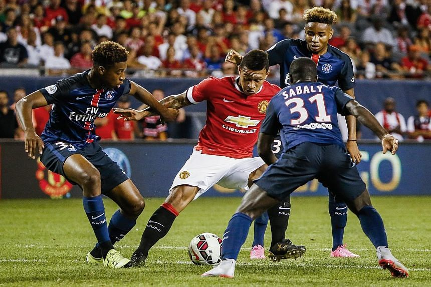 Manchester United forward Memphis Depay (in red) finds the going hard, surrounded by three Paris Saint-Germain players, in an International Champions Cup match in Chicago on Wednesday. In the game which the Red Devils lost 0-2, goalkeeper David de Ge