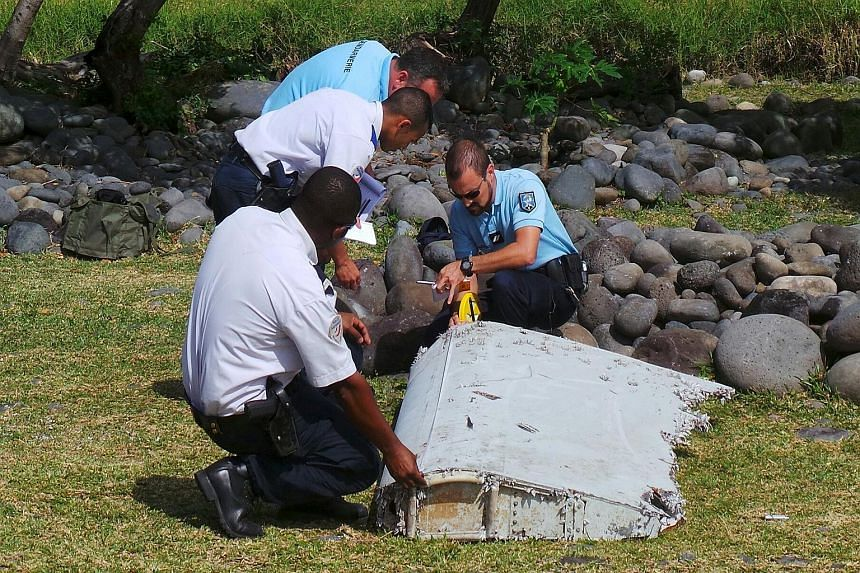 French police inspecting a piece of plane debris found in Saint-Andre, on Reunion island, on Wednesday. France's BEA said it was examining the debris, in coordination with Malaysian and Australian authorities.