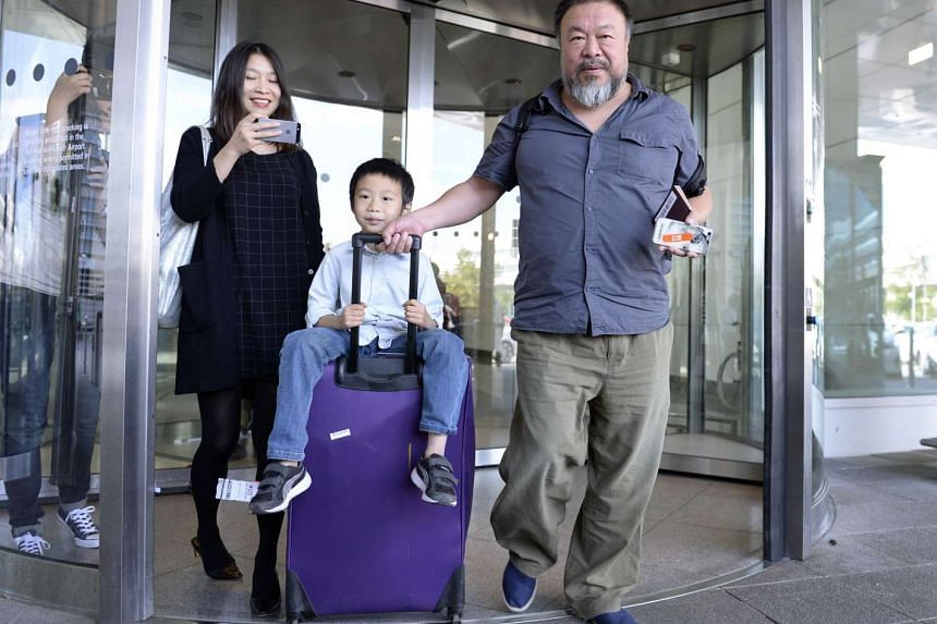 Chinese artist Ai Weiwei is accompanied by a boy and a woman as he leaves the Franz-Josef-Strauss airport in Munich.