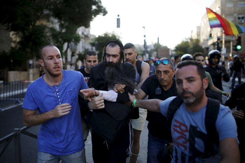 People detain after disarming an Orthodox Jewish assailant, after he stabbed and injured six participants of an annual gay pride parade in Jerusalem.