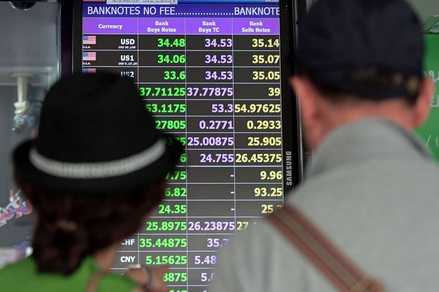 Tourists look at an electronic board electronic displaying current exchange rates at a shopping mall in Bangkok on July 27, 2015. PHOTO: AFP