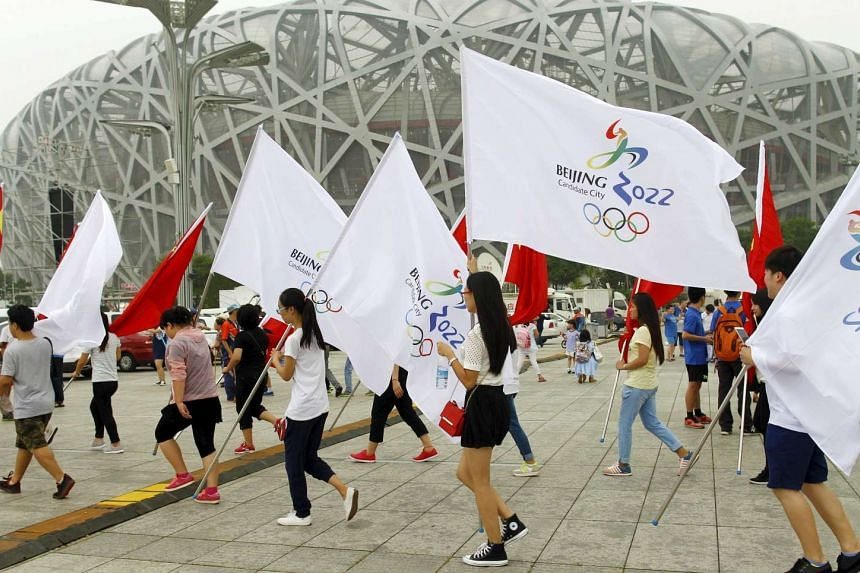 Participants holding Chinese national flags and Beijing 2022 Olympic flags walk past the National Stadium in Beijing, China, on July 30, 2015.