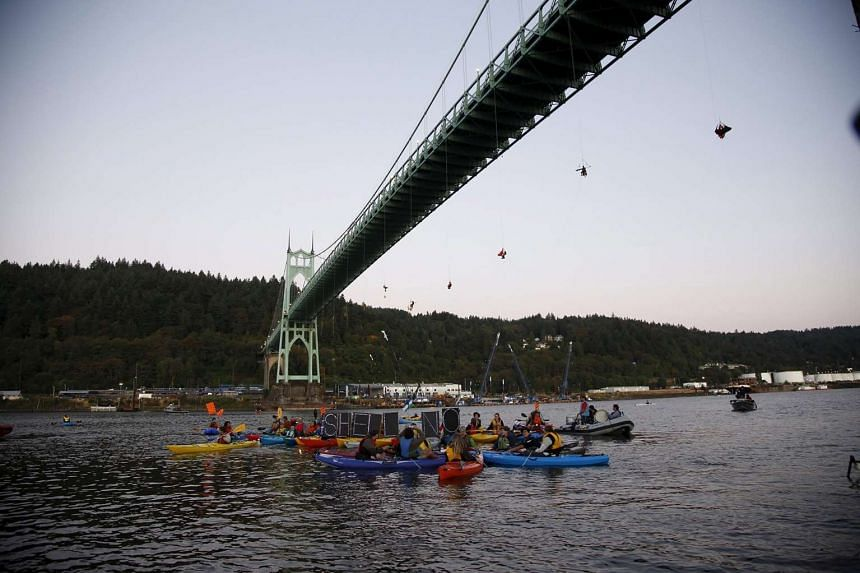 Greenpeace activists hang under the St Johns Bridge and kayakers gather in the Williamette River in an attempt to block the Shell leased icebreaker, MSV Fennica.
