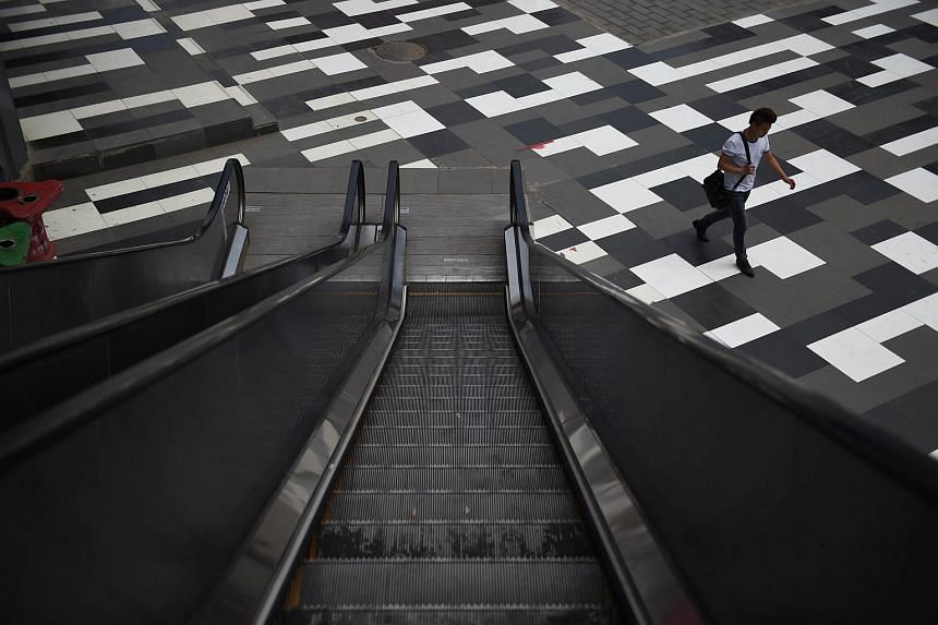 A man walks past an escalator at a shopping mall in Beijing on June 17, 2015.