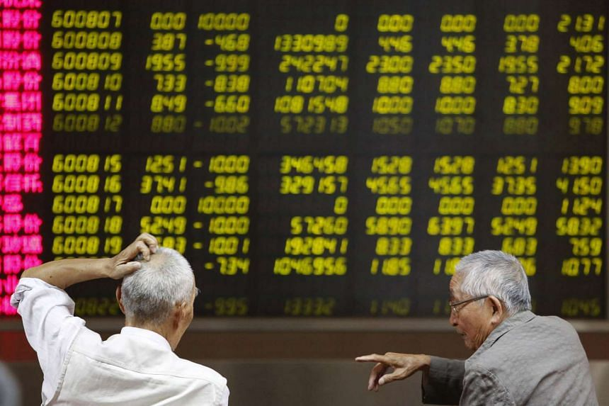 Investors chat as they watch a board showing stock prices at a brokerage office in Beijing, China, on July 6, 2015.