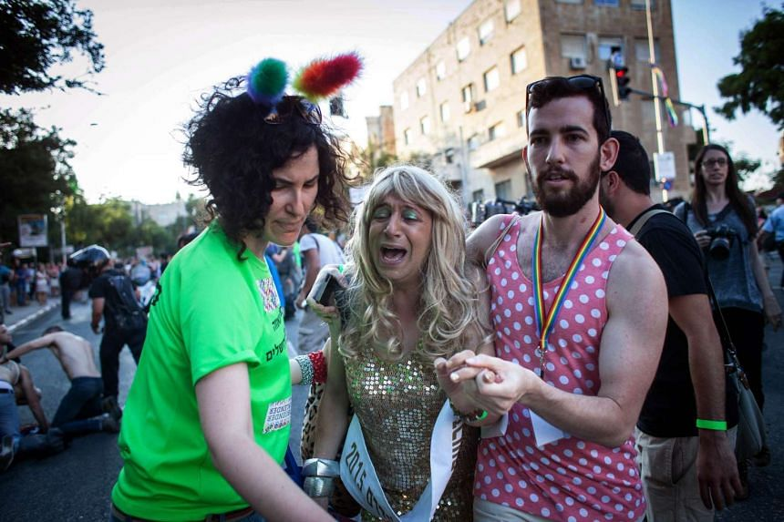 A participant of the Gay Pride parade reacts after Yishai Shlissel, an ultra-orthodox Jew, stabbed six people taking part in the march in central Jerusalem.